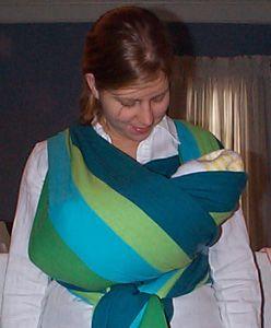 Un nudo alto pero hiperpresivo con bebé lateral. En esta fotografía el bebé es muy pequeñito por lo que no es lo óptimo.   Para usarlo de manera óptima y con silla de ruedas (ej) : - el bebé debería tener al menos los pies, sino las piernas por fuera desde la rodila.  - El bebé tenga más 3 meses y no se han detectado indicios de displasia de cadera.  Evitar el anudado abdominal.  La barbilla del bebé y su pecho no deben quedar pegados. Al menos 1 dedo de separación MINIMO.