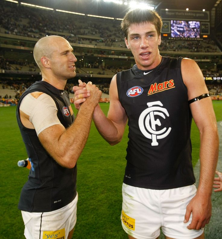 Chris Judd and Matthew Kreuzer celebrate after the Round 1 victory over Richmond the MCG in 2012.