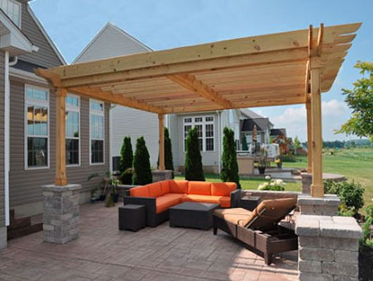 Bold modern furnishings create an inviting nook under this simple wooden pergola design. The stone used here can be repeated throughout the landscape for a feeling of repetition. Design by Morsellis Landscape Creations in Mantua, Ohio.