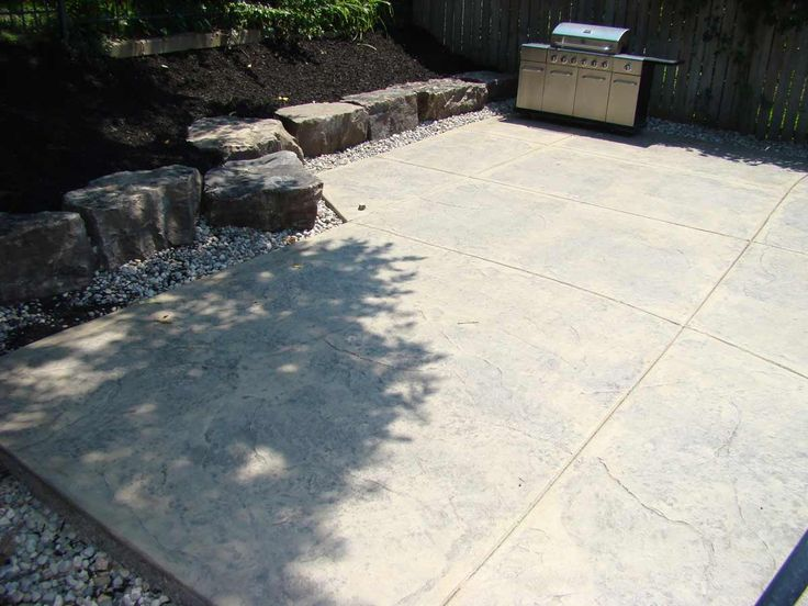 Decorative stamped, coloured concrete patio creates an inviting backyard space for entertaining.