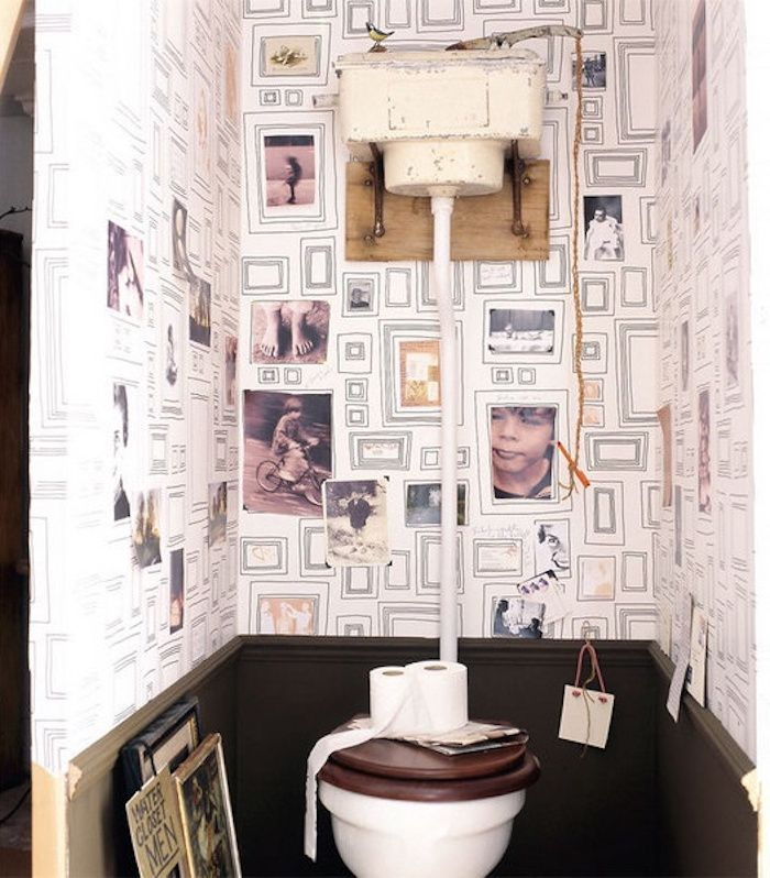small toilet with dark grey panelling, white wallpaper with many drawn frames, some decorated with black and white photos, plain white toilet seat, with dark wooden cover