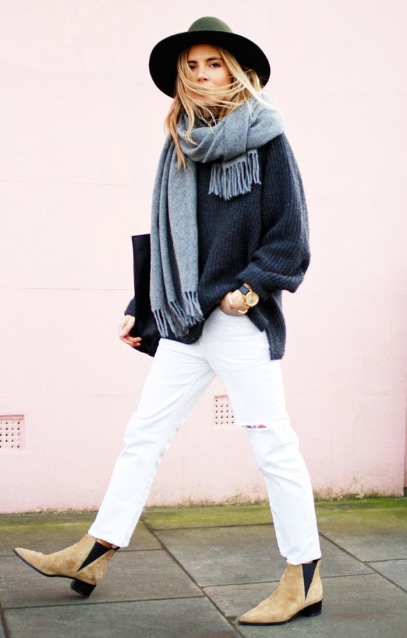 A sweater is worn with a gray scarf, cropped white jeans, suede boots, and a fedora