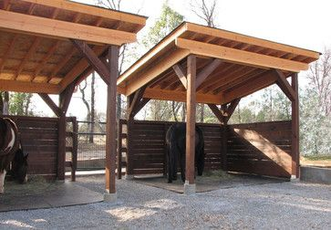 5-foot walls promote airflow and allow the horses to see over them. The roofs are composite shingles, which are much quieter than metal in the rain. The floors are rubber mats that are spiked into the ground, so the horses avoid ingesting any sand when eating
