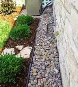 A rock maintenance strip around the house ... catches splashes, keeps siding clean and minimizes pests. Put your foundation plantings in front.