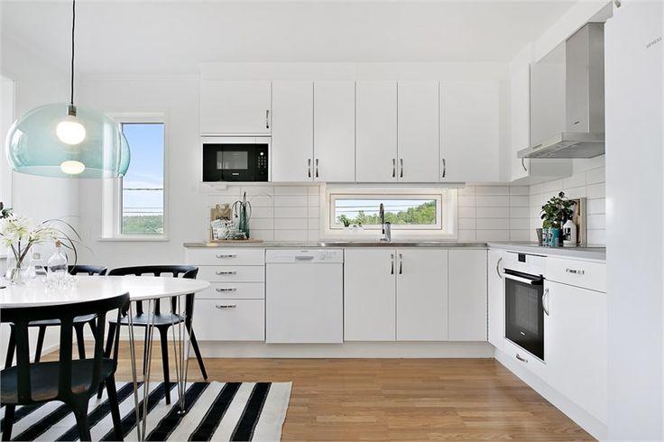 Kök i vinkel med köksinredning från Ballingslöv. Köket är inrett med stilrena släta köksluckor med handtag i borstad metall och praktisk rostfri arbetsbänk vid diskhon, som övergår i en tålig laminatskiva.