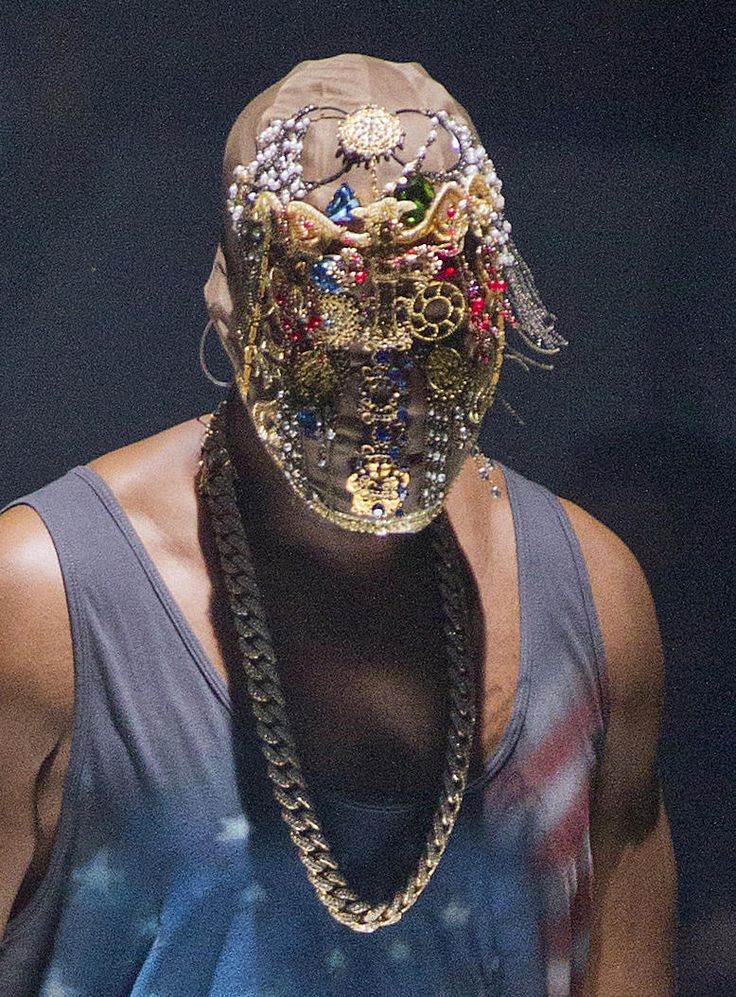 Kanye West Mask -- Jewelry is assembled on this mask to resemble a face. Gold circular accessories are positioned to cover Kanye's eyes as other pieces are situated over his nose and mouth. As assortment of multicolored stones accentuate the rest of the headset, including some draping chains.