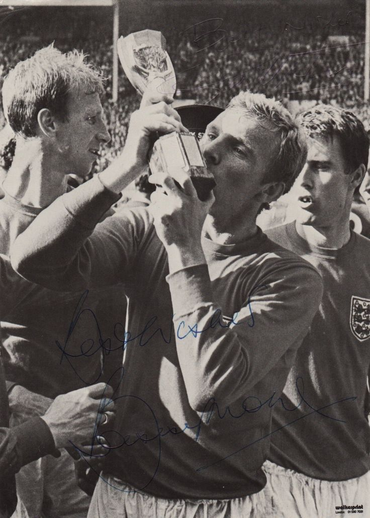 MOORE BOBBY: (1941-1993) English Footballer, Captain of the England World Cup winning team of 1966. Signed 6 x 8 photograph depicting Moore in a three quarter length pose kissing the Jules Rimet trophy following England's victory in the World Cup final at Wembley Stadium on 30th July 1966. In the immediate background the England players Jack Charlton and Geoff Hurst can be seen. Signed by Moore in blue ink to the image and also signed by Geoff Hurst at the head of the image.