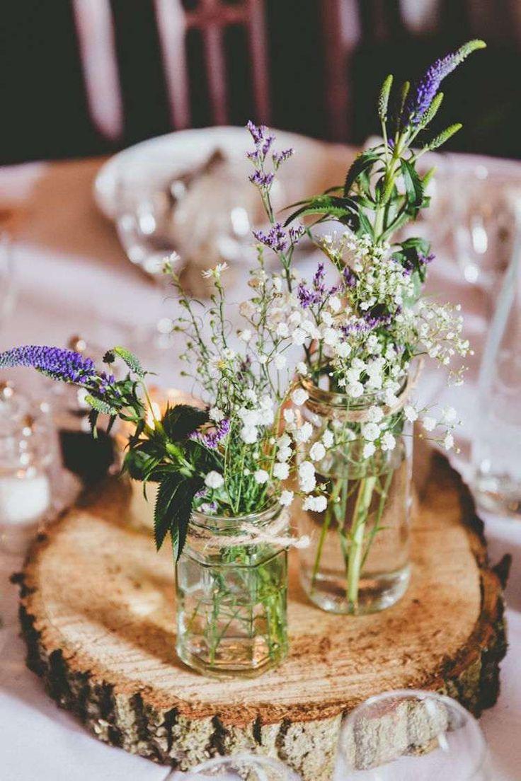petits bouquets en gypsophiles, marguerites et lupin en bocaux de verre sur un présentoir en bois
