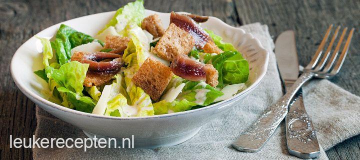 Caesar salad VOORGERECHT/BIJGERECHT – 25 MINUTEN – 4 PERSONEN *  Lekker recept voor de klassieke caesar salad met zelfgemaakte dressing en krokante knoflook croutons Ingrediënten Krop romeinse sla of 2 little gems Ongeveer 80 gram Parmezaanse kaas 8 sneetjes brood naar keuze 2 tenen knoflook Olijfolie om in te bakken Optioneel: 3 extra ansjovisfilets p.p.   Ingrediënten dressing: 2 eieren 3 tenen knoflook sap van ½ citroen klein bosje peterselie mespunt mosterd 4 ansjovisfilets + beetje olie…