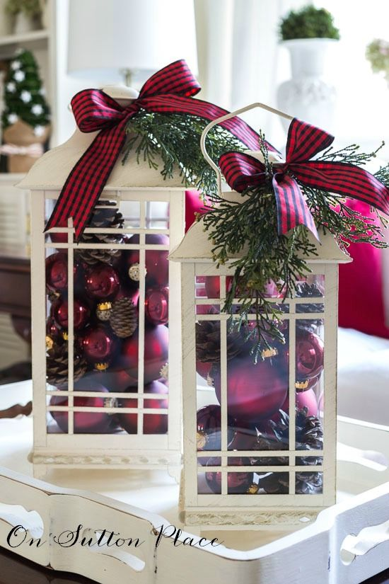 Christmas decor using lanterns | Fill with red ball ornaments and pinecones. Top with fresh or faux greenery and a fun bow!
