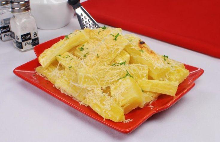 Foto com a receita de mandioca assada com queijo, disposta em um prato quadrado de vidro vermelho. Os pedaços de mandioca estão dourados e polvilhados com queijo ralado e salsa.