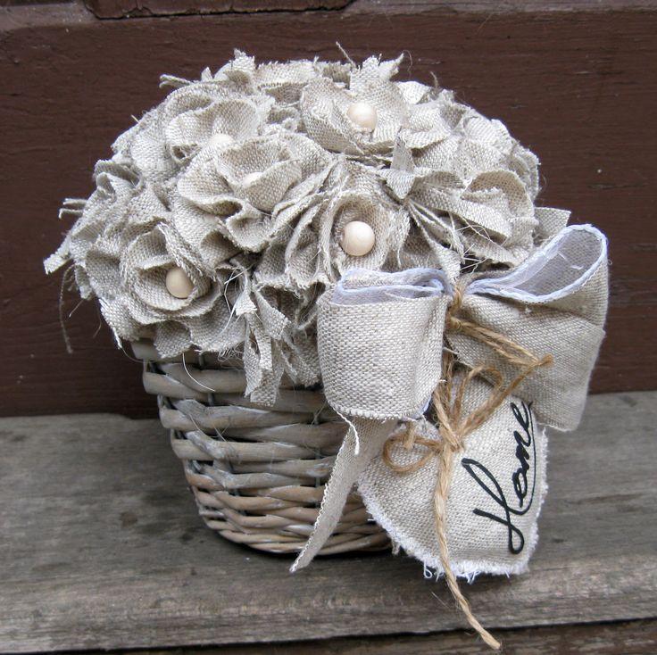 Košíček s květy Celoroční patinovaný proutěný košíček, výška dekorace 16 cm, šířka 19 cm, laděno do bílé a béžové barvy. Lněné květy s dřevěnými korálky, srdíčko s nápisem Home.