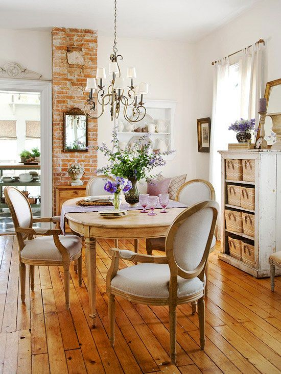 Happy space-- open bookshelf with baskets for storage, hardwood floor finish, washed bricks, chandelier, trim, dining table and chairs-- cozy, welcoming, and elegant.