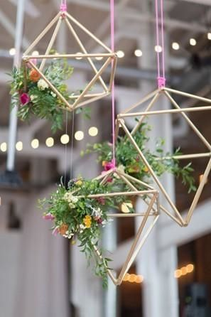 Gold geometric shapes with small colorful flowers and greenery hung from hot pink string for a modern wedding.
