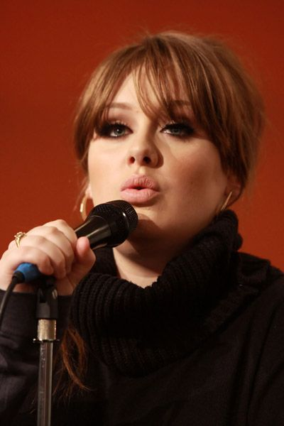 A close up shot of singer Adele holding a microphone, wearing a black turtleneck sweater and looking beautiful.