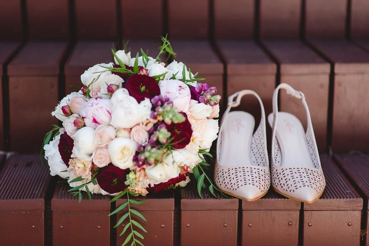 Soft pink and red roses bouquet and wedding shoes.