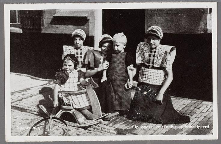 Drie vrouwen met gehaakte muts en grote brede kraplap, de middelste in de rouw en gedeelde rode doek geknield bij een staand jongetje in de rouw met zwart jurkje en donker fries schort. In het hobbelpaard een jongen met klapmuts, een jurkje en een licht fries schort. 1946-1960 K. Blokhuis #Utrecht #Spakenburg