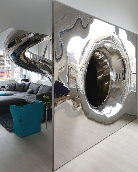 A tubular steel slide plummets through four storeys inside this penthouse apartment in New York