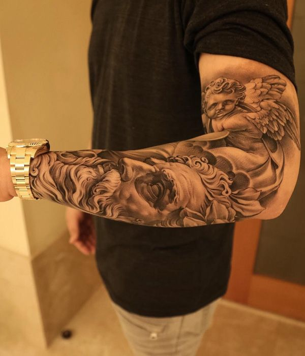 Well detailed sleeve tattoo, you can see a statue that resembles a young angel. Below him is another image which is a face of a man with long hair and beard that is also a carved statue itself.