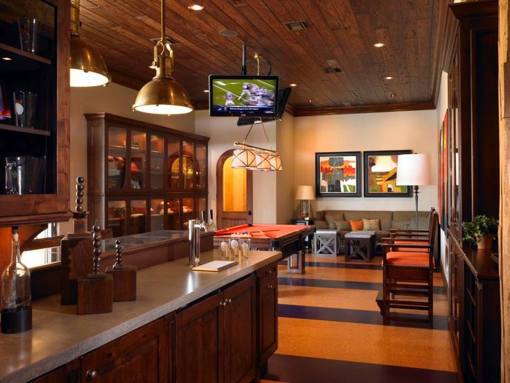 A Game Room With Bar Is Decorated Orange Tones And Warm Wood