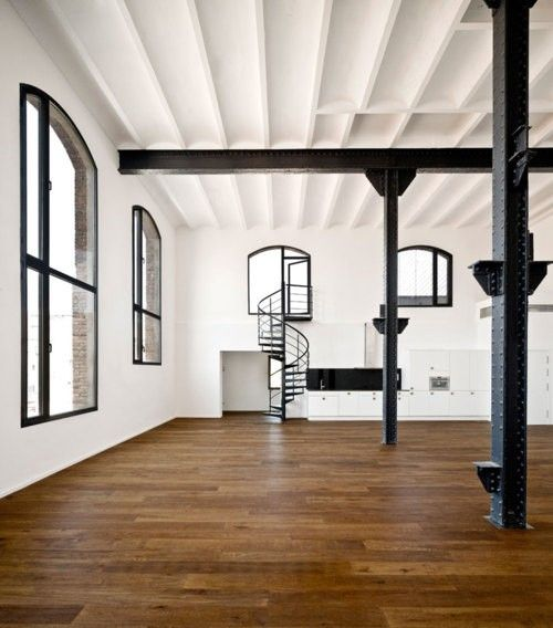 great loft space, black framed windows, stairs, pillars