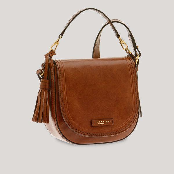 Die Leder-Handtasche The Bridge präsentiert sich mit elegantem und essentiellem Design. Mit ihrem minimalistischen und funktionellen Stil passt sie perfekt zu einem sportlichen oder einem Casual-Outfit. Front-Taschenpatte mit Druckknopf. Eine wahre Ikone mit Retro-Stil: The Bridge, das Ergebnis von reinem Handwerk.