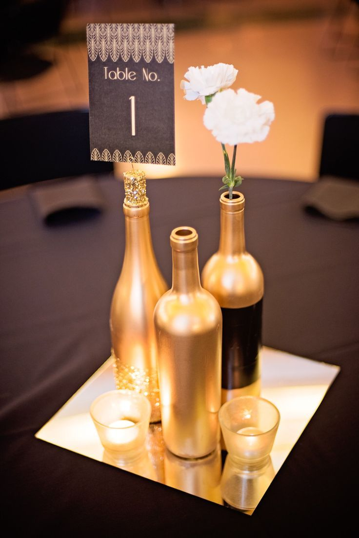 Gold and glitter wine bottles as the table centerpieces for weddings or corporate event. Black and gold Great Gatsby style table cards with white carnations, gold mirror plates and gold glitter votives