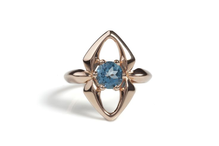 This ring features a beautifully faceted and striking deep sky blue topaz which is the center point to a hand carved and curvaceous design. £315