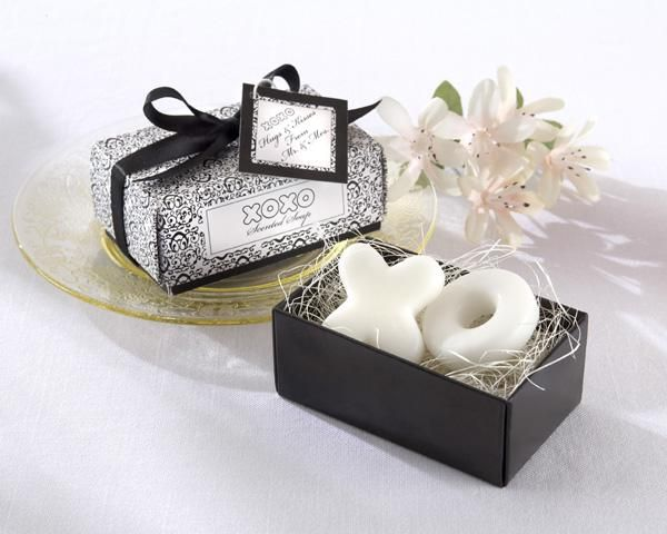 """Hugs & Kisses Soap Wedding Favor Set includes two soap wedding favors with a powder fresh scent. One soap is in the shape of an """"X"""" and the other is an """"O"""". They come nestled atop natural raffia in an intricately design black and white gift box. The gift box is wrapped with a black grosgrain ribbon that is tied into a bow at the top. The bow has a gift tag that reads """"Hugs & Kisses from Mr. & Mrs."""""""