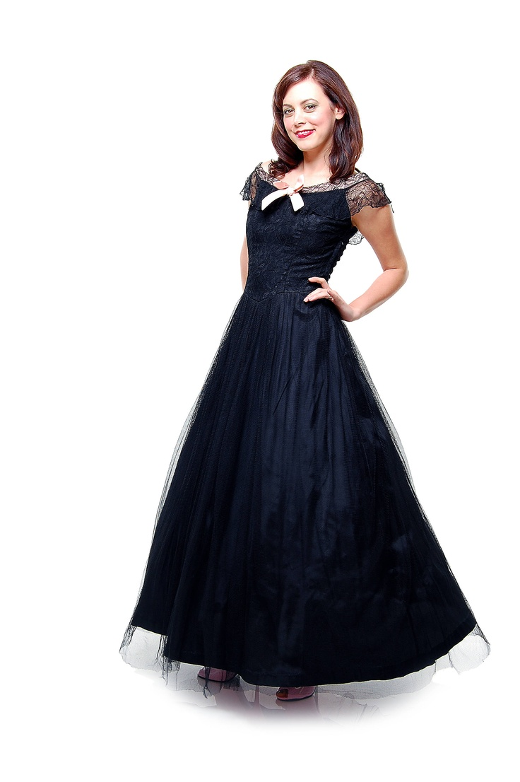 This full 1940's authentic vintage prom gown features black lace detailing that is sweetened up by a pink bow. Buy it at Unique Vintage.