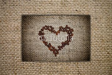 Heart of coffee beans on a burlap background