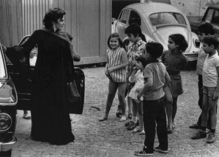 Amalia Rodrigues with children in the street
