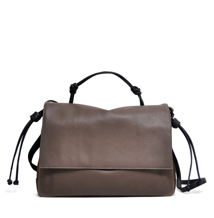 The Handheld in Taupe and Black from von Holzhausen featuring natural grained soft Italian leather with painted edges. Comes with removable crossbody strap, two open pockets on interior and removable signature wallet.