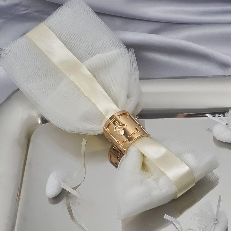 Μπομπονιέρα με ιβουάρ τούλι και ροζ χρυσό κρίκο πετσέτας με χαραγμένο πέταλο και μάτι και 5 κουφέτα Χατζηγιαννάκη. Η τιμή είναι ενδεικτική και καθορίζεται από την ποσότητα.