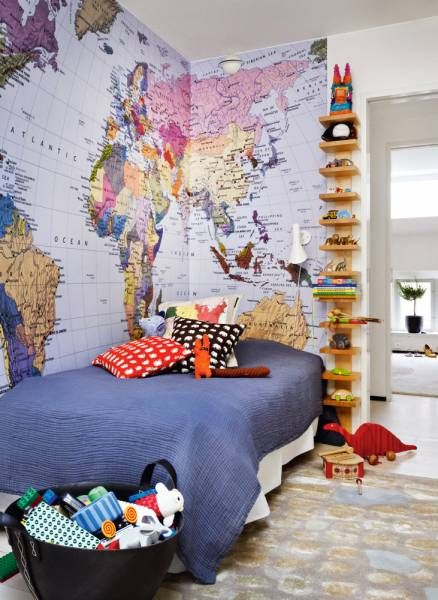 World atlas walls. Little brother's room with a reptilian patterned carpet in the design of Victoria Hamberger for Glowb. Wall lamp by Arne Jacobsen, shelf Pilaster by John Kandell, Källemo. Bedspread from Society, pillows from Swedish tin. The map shows the family's large travel interests, both at work and at play