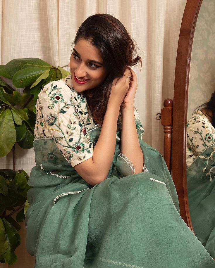 Sage green organza saree with pearl white V necked hand embellished blouse. Laun…
