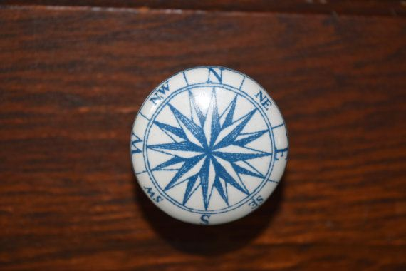 This ceramic drawer knob is white with a blue compass rose on the face. These drawer knobs will transform your furniture to your own unique piece.