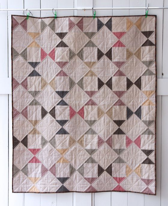 essex linen quilt front sixty 5.5″ hourglass blocks and sixty 5.5″ squares out of the plain linen. The quilt is 10 blocks wide by 12 blocks long. The finished quilt measures about 50″ x 60″.