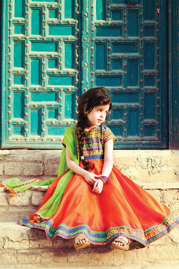 This adorable orange circular cut chanderi kurta comes with printed yoke and mirror work. Paired with an orange knit churidar and lime green net dupatta to give your doll a gorgeous dress up.