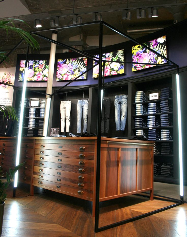Each window was based on a palette of colours: pink, green and yellow of hanging wisteria. Tenn also produced a metal ceiling grid and a lightweight free-standing backdrop for each of the windows. All of the faux wisterias were hung by hand, draping over the window mannequins. The interior scheme comprised of four standing metal structures and a flower cart, all in a matt black powder coated finish. These were dressed on site with additional faux foliage and used throughout the store.