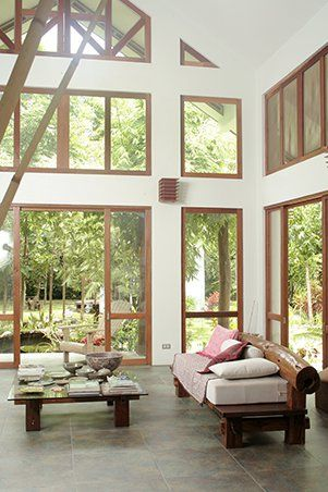 Located in Batangas, this home has glass doors, indoor ponds, and unroofed areas that welcome both sunshine and rain showers right into the space. These same elements complete the outdoor vibe that characterize the nature-inspired abode. The living area has high ceilings, big windows, and wooden furniture that create an airy, tropical feel. From the area, one can see the lanai as well as the pond that runs alongside an uncovered walkway that cut through the center of the house. Click here to…