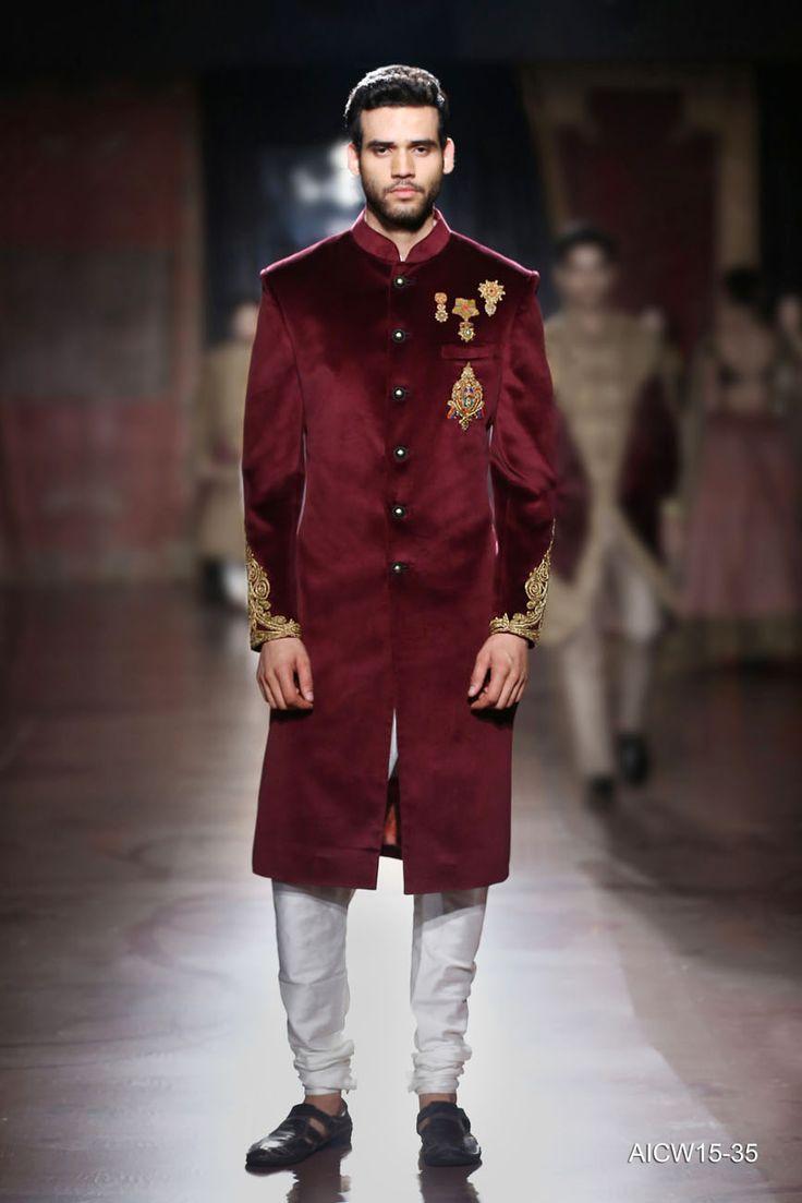 Maroon velvet sherwani featuring zardozi embroidered crests paired with a silk kurta-churidar