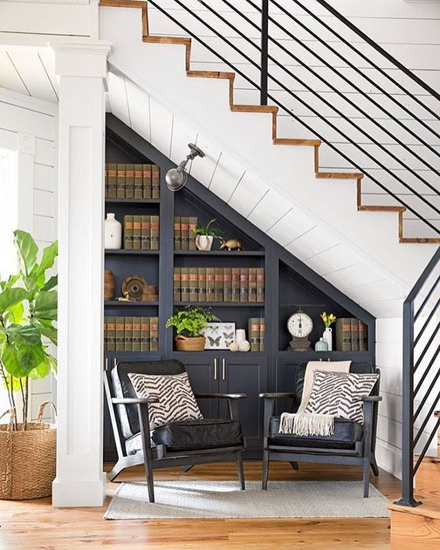 understairs book shelves with chairs, mini library with dark navy blue and white walls and ceiling.