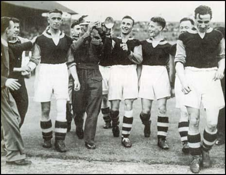 The West Ham team celebrate victory in the 1940 War Cup Final. Left to right,Charlie Bicknell, Norman Corbett (in uniform), Ted Fenton, (unknown) and Len Goulden.