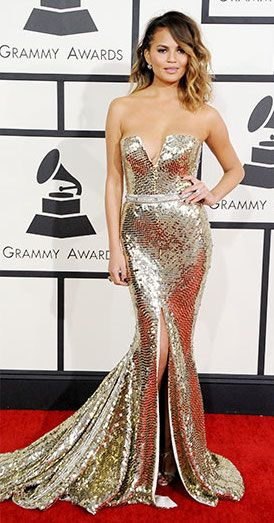 Chrissy Teigen wears a Johanna Johnson gold strapless, deep v fully sequined gown