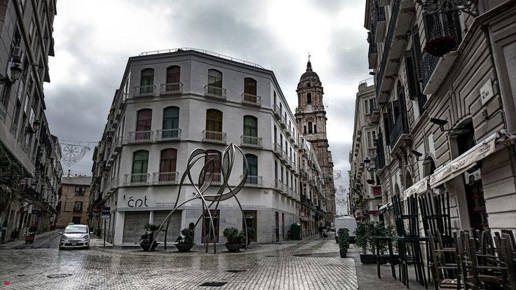 La torre de la catedral de Málaga se asoma al la plaza del Siglo para ver la escultura Panta rie.