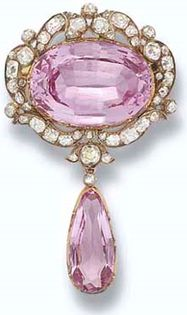 HRH Princess Margaret Pink Topaz Pin - Antique Pink Topaz and Diamond Pendant Brooch. The central oval pink topaz within a scroll border of cushion-shaped diamonds suspending a detachable topaz and diamond drop, mounted in silver and gold. Circa 1860. This brooch was purchased by H.R.H. The Princess of Wales, later H.M. Queen Mary, in 1901. Sold at Christie's, London in 2006. - http://www.thetudorswiki.com/page/Jewellery+of+Today%27s+British+Royalty+-+Page+2#