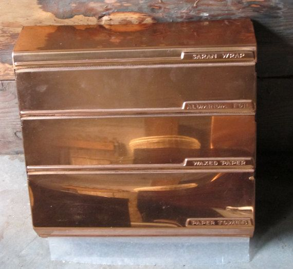 The perfect storage unit to get chunky boxes out of your kitchen drawers! Easily conceals and stores your Saran Wrap, Aluminum Foil, Waxed Paper and Paper Towels roll. This organizer has an amazing flashed copper color and is in amazing vintage shape! The perfect kitchen accessory