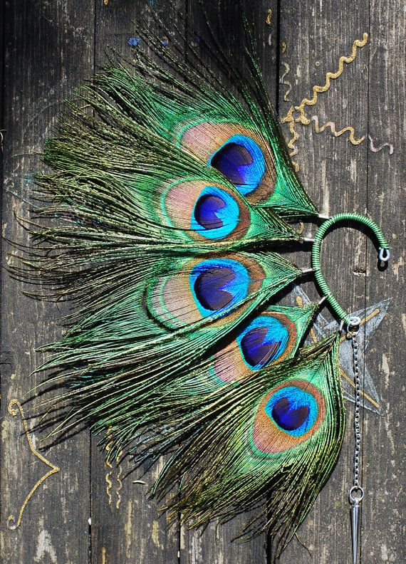 This beautiful feather ear   cuff was made using five peacock feathers and chain with spike. The basis is wrapped with green wire.    I ship items within