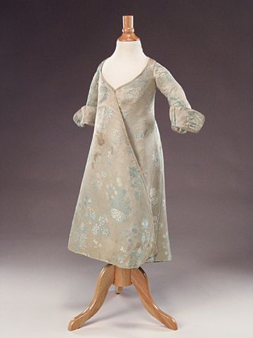 Child's banyan, England, textile: 1710, garment: c. 1750. Grey silk brocade woven with a stylized floral design in pale blue and white, lined with indigo-dyed cotton plaid.